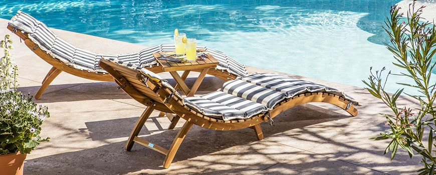 Two chaise lounges with striped cushions, poolside.