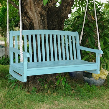 A blue outdoor swing, suspended by rope from a tree