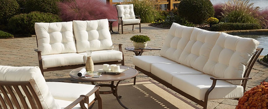 A bronze-tone aluminum conversation set with white outdoor cushions