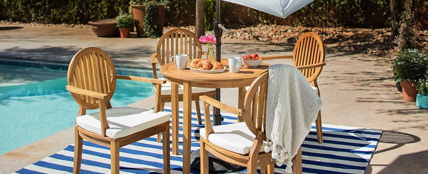 An outdoor dining set, poolside, with a blue-and-white outdoor rug and white outdoor umbrella