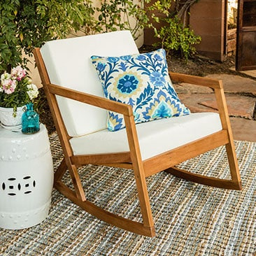 A wood rocking chair with white outdoor cushions, with an ikat pillow, white side table, and multi-colored outdoor rug