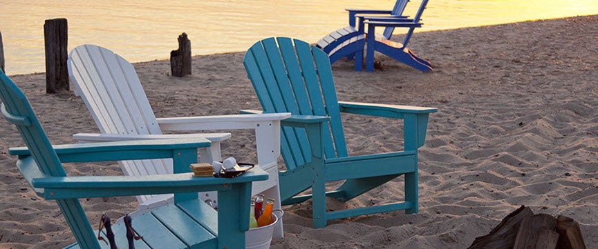 Four polywood Adirondack chairs in assorted colors, on the beach.