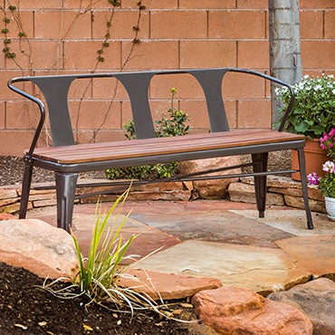 A gray metal and wood bench, on a flagstone patio