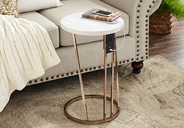 Metal C table with a glass top beside a sofa