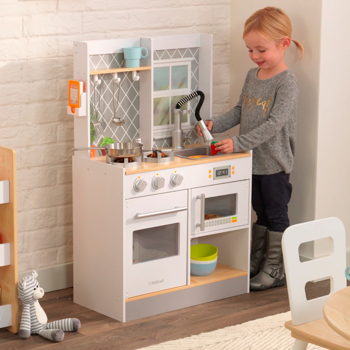 A young girl pretending to use the sink of a white toy kitchen in a tidy playroom with toys you can find on Overstock