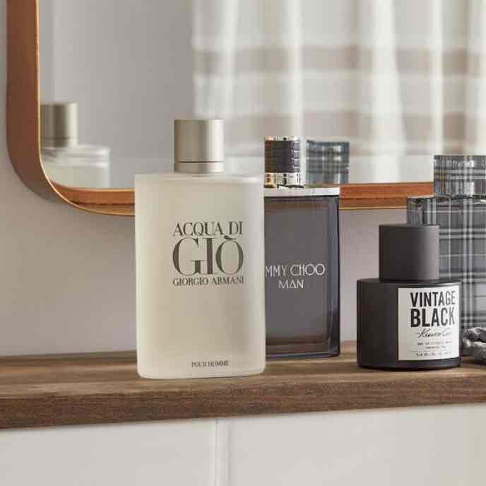 A closeup of a bathroom shelf with cologne available online at Overstock