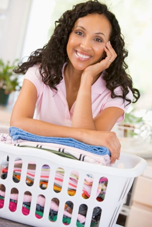 Woman enjoying her hamper full of clean laundry