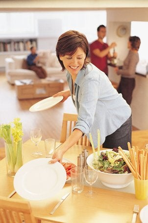 Woman sets a dining table