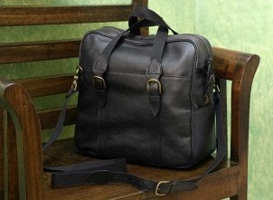 A handsome black leather business case sitting on a chair