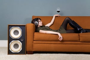 A young woman enjoying wine and music in her basement