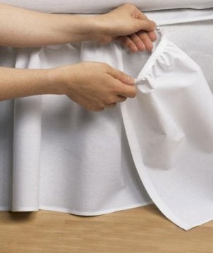 Woman putting a bedskirt on a bed