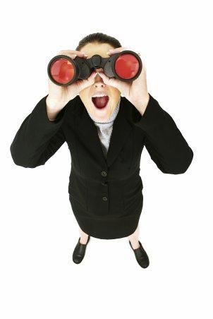 Woman looking up through binoculars