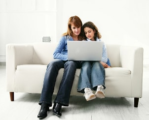 Mom and daughter looking at a laptop together