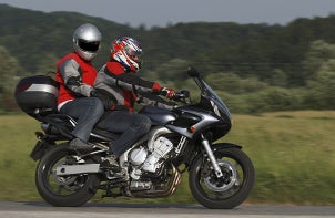 Two people riding a motorcycle and wearing protective motorcycle gear