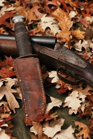 Hunting knife and shotgun in autumn leaves