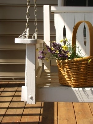 White wooden porch swing holds a basket of flowers