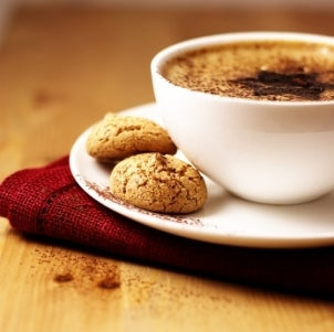 Delicious cup of coffee with cookies