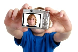 Boy taking a photo with a small digital camera