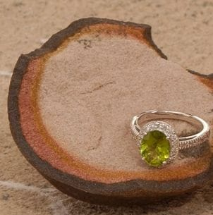 A green cubic zirconia ring on the beach