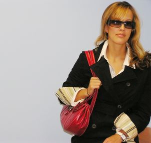 Business woman carrying a red handbag to work