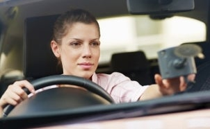 Woman using a GPS in her car
