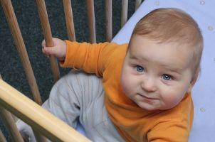 Adorable baby boy in a playard