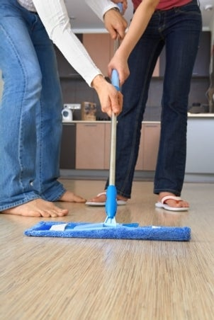Happy couple cleaning a floor with blue microfiber mop