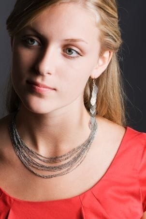 Blonde woman wearing a sterling silver necklace and earrings