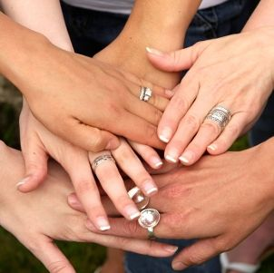 Sterling silver rings on six female hands
