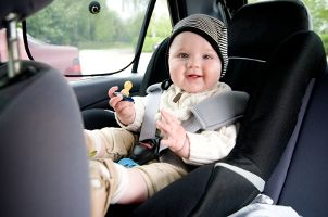 Cute baby smiling while in a car seat