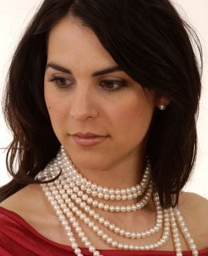 Woman wearing pearl stud clip earrings and a pearl necklace