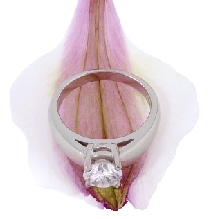 Solitaire diamond ring with a prong setting on a pink flower petal
