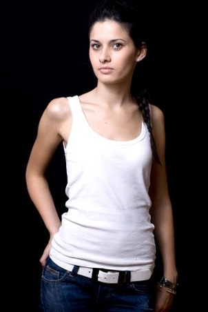 Beautiful model wearing a white tank top, jeans and a Calvin Klein watch
