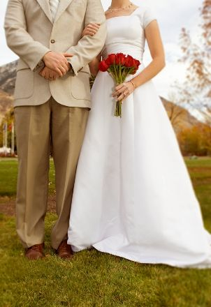 Bride and groom standing together on a lawn