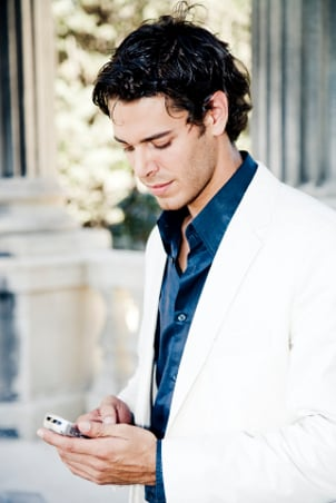 Man in a suit checking his cell phone