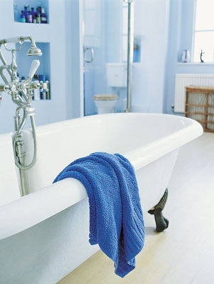 Claw-foot tub in a light blue bathroom