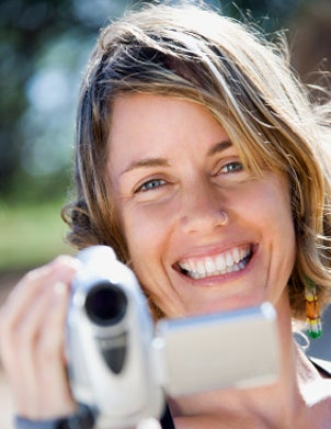 A smiling woman filming with a camcorder