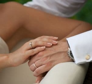 A bride and groom wearing wedding bands and holding hands