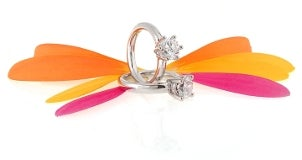 Two diamond engagement rings and a handful of colorful flower petals form a butterfly