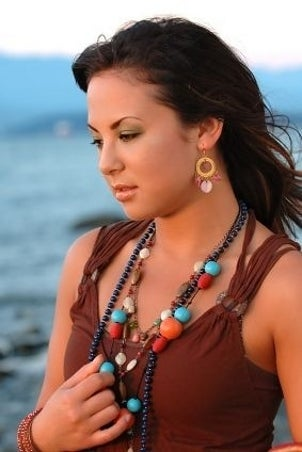 A cute girl wearing turquoise jewelry at the beach