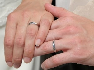 Bride and groom wearing matching platinum wedding bands