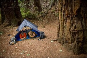 Couple camping in sleeping bags and a tent