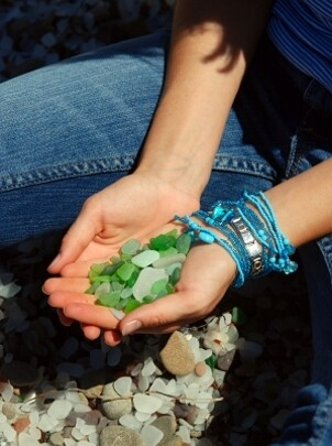 A woman wearing layers of crystal turquoise bracelets and holding green rocks