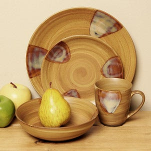 Casual stone dinnerware and a pear