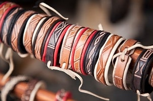A stack of men's leather jewelry for sale