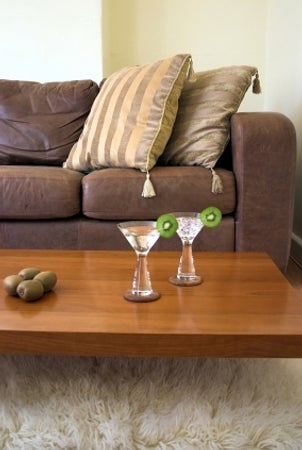 Wooden cocktail table with two kiwi martinis on top