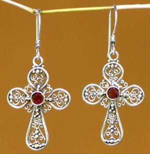 A pair of silver and ruby cross earrings hanging on a branch with a yellow background