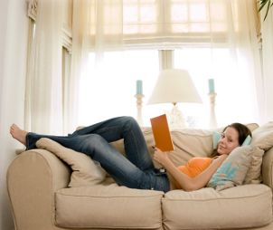 Woman on a couch, wearing stylish jeans