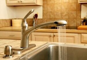 Silver soap dispenser pump by a kitchen sink