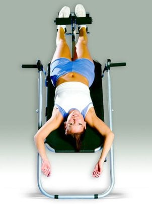 A woman getting the best inversion table workout of her life